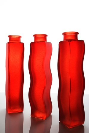 houseware: Red vases on a reflective surface with back light.