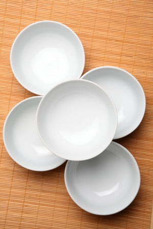 placement: Five white bowls photographed from the top over a wooden placement background.