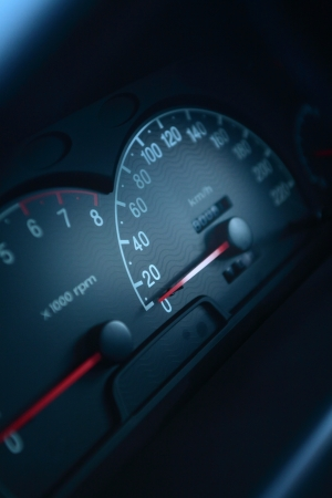 A closeup on the dashboard of a modern car with focus on the speedometer. photo