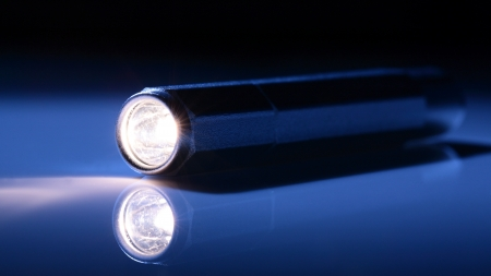 torchlight: A pocket light torch, flashlight on dark blue background with a spotlight on it. Stock Photo