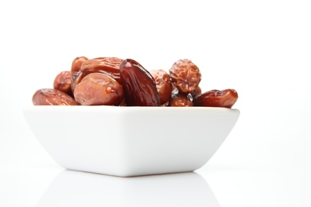deglet: Photograph of sugar covered and dried date (deglet noor sub-type) palm fruits in a bowl. The fruit is also known as Phoenix dactylifera. This particular sort of the fruit is grown in Algeria and Tunisia.