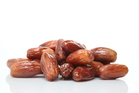 dry fruit: Photograph of sugar covered and dried date (deglet noor sub-type) palm fruits on white with a natural reflection. The fruit is also known as Phoenix dactylifera. Stock Photo