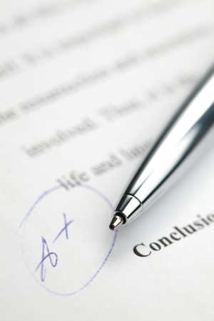 essay: A stylish pen laying over a paper graded with the highest possible grade - A+. Stock Photo