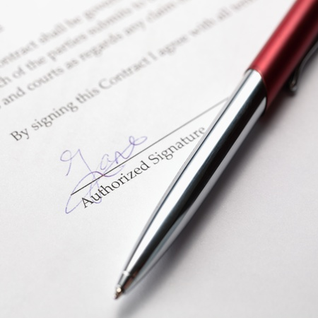 A stylish pen laying over a signed contract. Stock Photo