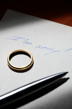 separating: A note saying I am sorry! with a wedding ring and a pen over it. A concept about divorce or breaking up of marriage.