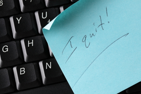 A blue sticky note on a computer keyboard with text I quit!. Stock Photo