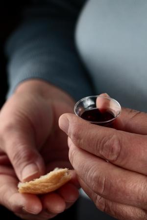 Idős kaukázusi nő kezével egy kis közösségben csésze borral és egy darab kenyeret. Stock fotó
