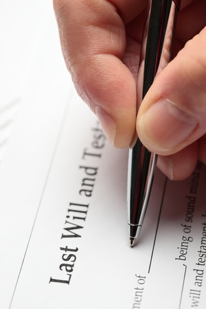 An elderly hand filling out a last will and testament document  Stock Photo