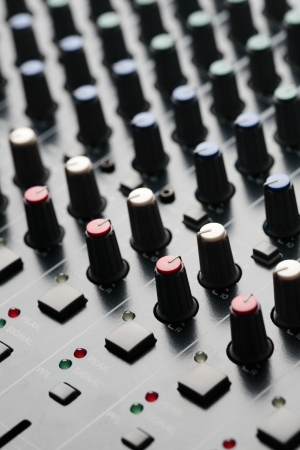 A closeup image of an audio mixer under dramatic light  photo