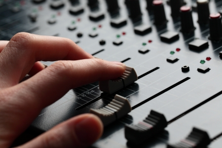 A closeup image of a female hand adjusting the volume of a sound mixer  photo
