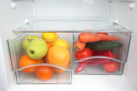 Fruits and vegetables in two containers in a modern fridge - a healthy food concept  Stock Photo
