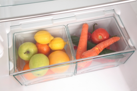 Fruits and vegetables in two containers in a modern fridge - a healthy food concept  photo