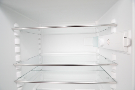 A clean and empty refrigerator with white walls and glass shelves. No products inside. photo
