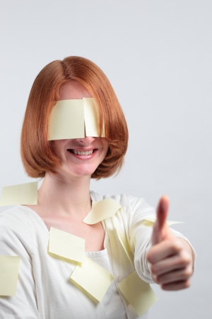 A smiling woman with sticky notes all over her giving a thumbs up sign. photo