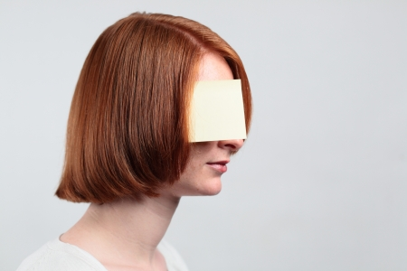 A serious woman with a sticky note covering her eye. photo