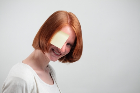 A smiling woman peeking behind a sticky note placed over her eye. photo