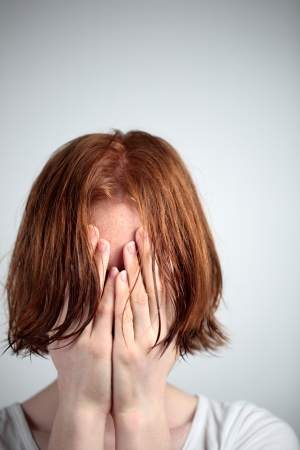 be wet: A young redhead female with wet hair covering her eyes - could be because of depression, stress or fear.