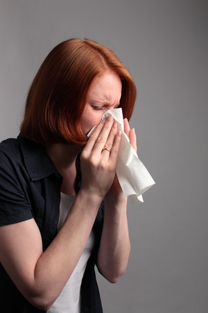 hanky: A young woman blowing her nose - because of an allergy or a cold. Stock Photo