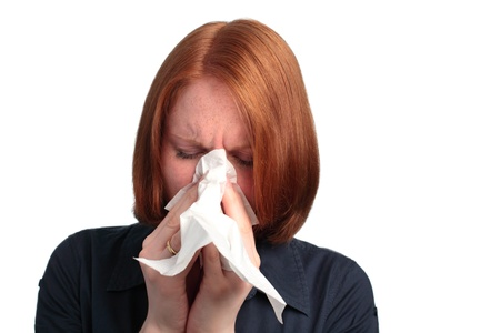 A young woman blowing her nose - because of an allergy or a cold. Stock Photo - 20442889