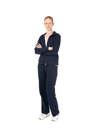 average woman: A young woman in sports clothing with folded hands smiling at the camera. Could be a fitness trainer, trainee or just an average active person. Isolated on white.