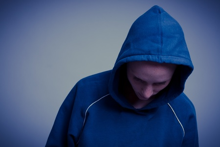 hooded top: A young Caucasian woman with attitude dressed in a blue hooded top looking down.