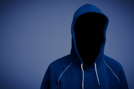 A faceless, incognito or anonymous, person in a hooded blue top.