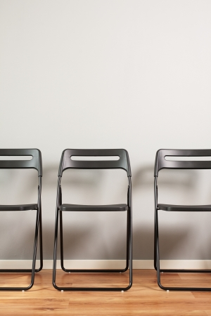 claen: An empty and claen waiting room - a row of foldable black chairs against a gray wall.