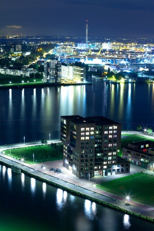 maas: A night photograph of part of the city of Rotterdam along the Maas river.