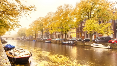 Houses, boats and a canal in Amsterdam, photographed on a foggy morning during the autumn season