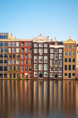 The facades of a row of typical Amsterdam houses along the water canal. photo