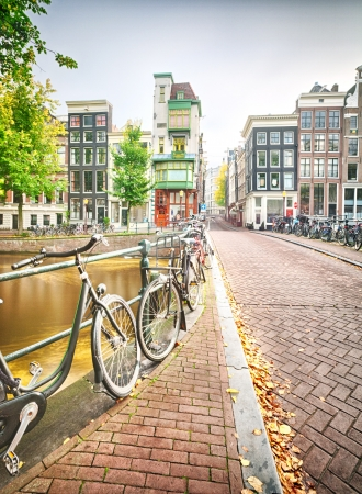 An empty street in Amsterdam, the Netherlands with typical houses and many bicycles parked on the side of a bridge which crosses over a canal  photo
