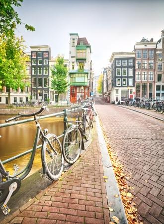 Egy üres utcán Amszterdamban, Hollandiában a jellegzetes házak és sok kerékpárok parkolt oldalán a híd, amely áthalad a csatorna