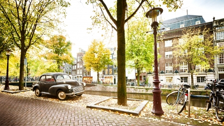 canal house: An autumn scene in Amsterdam, the Netherlands - a retro car is parked near a water canal