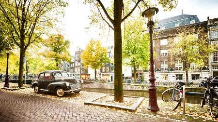 Een herfst scène in Amsterdam, Nederland - een retro auto wordt geparkeerd in de buurt van een waterkanaal