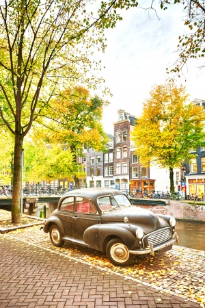 An autumn scene in Amsterdam, the Netherlands - a retro car is parked near a water canal