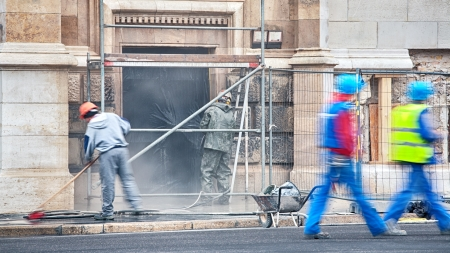 old building facade: Construction workers at a site where a building is being restored cleaned  Stock Photo