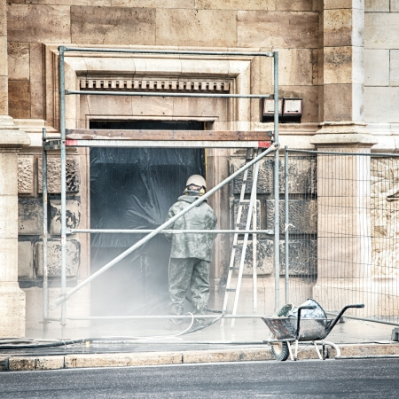 A worker restoring the facade of an old stone building with a pressurized water gun