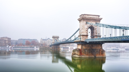 The famous Chain Bridge  Széchenyi lánchíd  crossing the Danube river in Budapest, Hungary  Photographed on a misty morning from the Buda side of the city