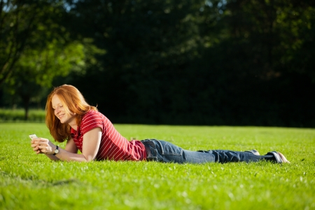 Young woman laying on green grass in a park and using a mobile phone. photo