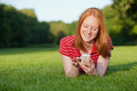 An attractive young Caucasian woman using a mobile phone while laying relaxed in a park. Stock Photo