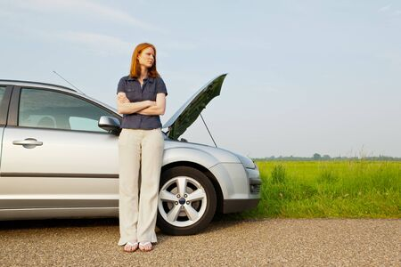 road assistance: A young female driver having car troubles on the road waiting for road assistance.