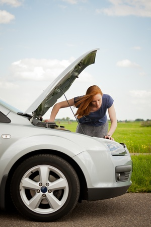 A young female driver inspecting her car with the hood or bonnet open. photo