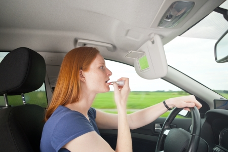 inattentive: A young Caucasian female driver putting on makeup and looking at the mirror while driving down the road. Serves for illustrating dangerous driving or similar concepts. Stock Photo