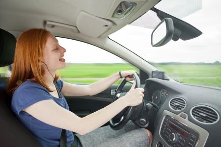 cantando: Una atractiva joven que conduce un coche de una manera descuidada - escuchar música con auriculares y cantando o hablando con el teléfono. Sirve para ilustrar conducción peligrosa o conceptos similares.