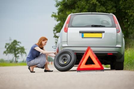 若い女性ドライバーの彼女の車のタイヤがパンクを変更します。