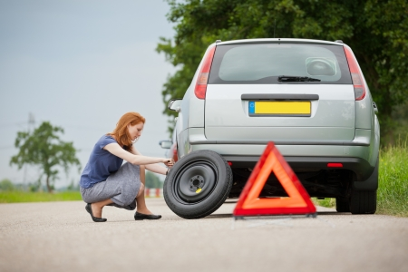 Young female driver changing a flat tire on her car.