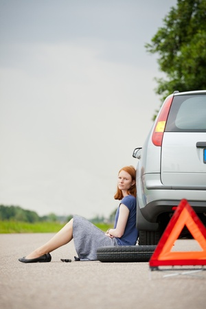 A sad or unhappy female driver sitting against her car which has a flat tire.