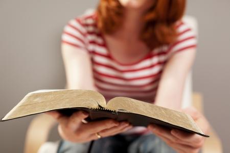 大型聖書を読む若い女性のクローズ アップ。 写真素材