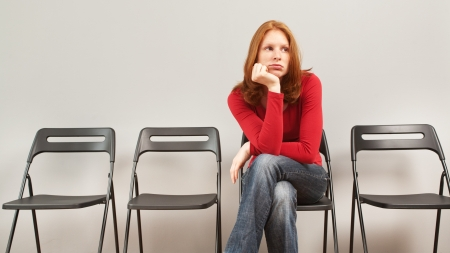 A young woman sitting in an empty waiting room and looking bored  photo