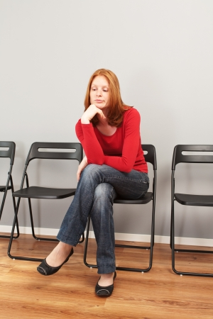 tedious: A young woman sitting in an empty waiting room and looking bored  Stock Photo